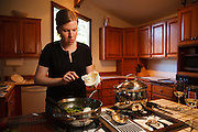 USA, Oregon, Eugene, young woman adding mascarpone to dinner. MR