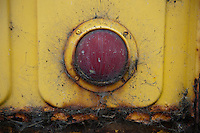 A rusted old yellow pick-up truck tail light.