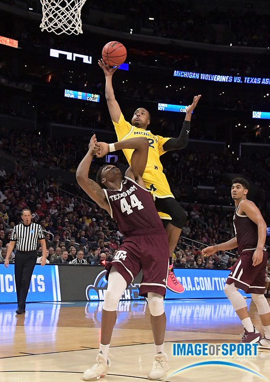 Michigan Wolverines guard Muhammad-Ali Abdur-Rahkman (12) shoots the ball as Texas A&M Aggies forward Robert Williams (44) defends in the seocond half during a West Regional semifinal of the NCAA men's college basketball tournament, Thursday, March 22, 2018, in Los Angeles. Michigan defeated Texas A&M 99-72.