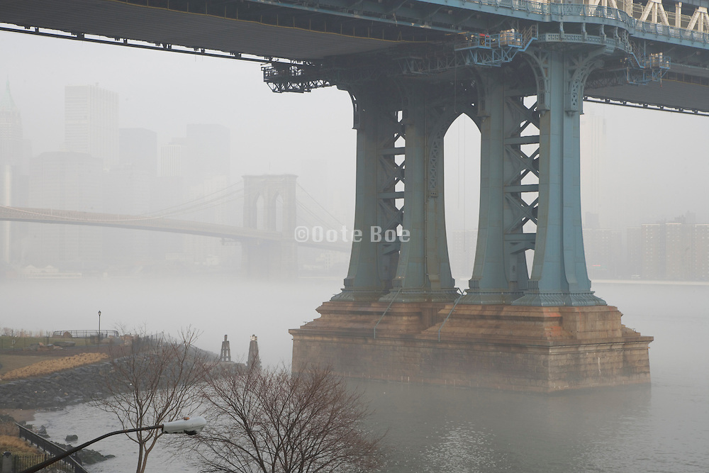 Brooklyn Bridge with Manhattan Bridge pillar in the foreground during a morning fog