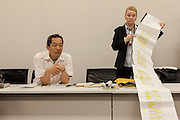 """Rape Survivor and activist, Catherine """"Jane"""" Fisher (right) shows a 6 metre long list of sexual crimes against women that have taken place in Okinawa since 1945 at a press conference to publicise her book in the First Office Building of the Members of the House of Representatives, Nagatacho, Tokyo, Japan, Friday July 18th 2014. Ms Fisher was raped near Yokosuka US Naval Base in Kanagawa in 2002 and has been campaign for the rights of rape victims in Japan since after finding the US Military and Japanese police obstructive and uninterested in bringing her attacker to justice."""