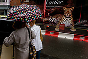 Friends sheltering from April rains under a spotted umbrella walk past a hoarding featuring a leopard for a reopening Cartier shop in New Bond Street, one of two centres for the jewellery industry in the capital. The coincidental patterns on the leopard and the brolley seem comical. Cartier S.A., commonly known as Cartier is a French jeweller and watch manufacturer. The corporation carries the name of the Cartier family of jewellers whose control ended in 1964. Pierre Camille Cartier opened and managed the London Cartier store in 1902.