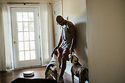 """BIRMINGHAM, AL – SEPTEMBER 4, 2020: Jonathan Perez, 31, greets his dogs at the entrance to his home in Hoover.<br /> <br /> As the coronavirus pandemic continues to grow in the United States, the cost of recovery from Covid-19 has varied considerably for Americans. Jonathan Perez, 31, contracted Covid-19 and was admitted to a nearby hospital in Birmingham, where his condition quickly worsened. """"They didn't think I'd make it,"""" Perez said. """"I'd said my peace."""" Fortunately Perez recovered, but he'd incurred medical bills in excess of $50,000. The uninsured Marine veteran was told his entire bill would be covered by the hospital using funds from the CARES Act. In the end, he ended up paying around $800. Perez, who has been virus-free for about a month, still suffers from fatigue. He spends his time trying to recover full use of his lungs by walking his dogs several times a day. """"I'm just thankful to be here,"""" he told me."""
