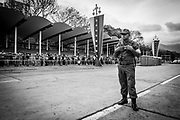 """A military looks at people waiting in queues to visit the remamins of Venezuela's President, Hugo Chávez in Caracas on the 9th March 2013. The queues to visit the Chávez lasted days and the waiting period could be over 24 hours period as thousands went to pay their last respects. Chávez ruled Venezuela for 14 years, passed away on the 5th March 2013.  He revolutionized not only his nation but also other countries in Latin America, with his political views and what he called the """"21st Century Socialism"""", supported by the petrodollars from Venezuela's massive oil-reserves."""