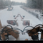 An oncoming vehicle seen through the windscreen of a grader driven by Chad Henry as he ploughs the roads of his community to clear them after a snow fall at the Ochiichagwe'Babigo'Ining Ojibway Nation reserve (also known as the Dalles First Nation) in Northern Ontario, Canada on 14 December 2016. Henry is responsible for operations and maintenance tasks on the Nation's reserve, but in 2013, together with a council of the community's youth, he initiated a project to erect a tower to bring broadband Internet access to the reserve.