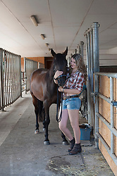 Young woman stroking her brown horse in stable, Bavaria, Germany