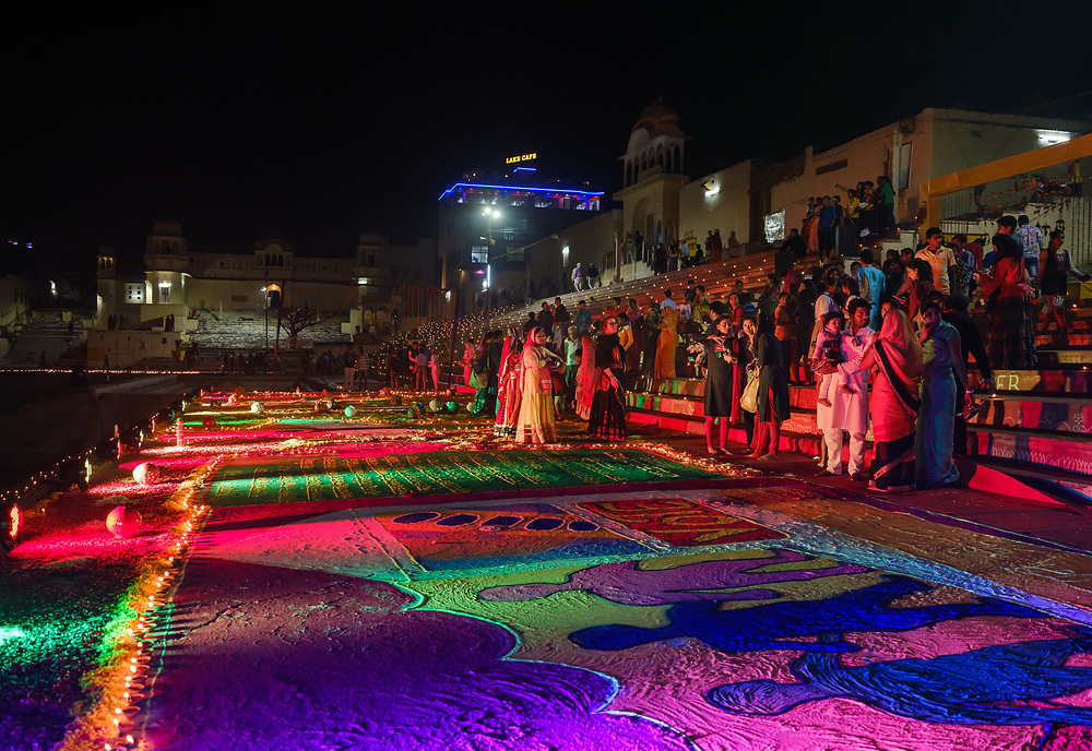 PUSHKAR, INDIA - CIRCA NOVEMBER 2018: Woman walking in the Pushkar Ghats during the opening ceremonies of the Camel Fair. It is one of the world's largest camel fairs. Apart from the buying and selling of livestock, it has become an important tourist destination. The city of Pushkar is a pilgrimage site for Hindus and Sikhs.