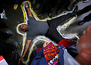 A protestor lays on the ground with a chalk outline marking his position during a demonstration at the Ferguson Police Department in Ferguson, Missouri, October 13, 2014.  Hundreds of protesters converged in the pouring rain on the Ferguson, Missouri, police department on Monday as they launched another day of demonstrations over the August killing by police of an unarmed black teenager. REUTERS/Jim Young (UNITED STATES)