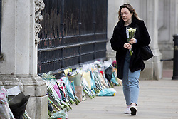 © Licensed to London News Pictures.10/04/2021. London, UK. A woman places flowers in front of Buckingham Palace. Yesterday Buckingham Palace announced that Prince Philip The Duke of Edinburgh passed away in the morning at Windsor Castle . Photo credit: George Cracknell Wright/LNP