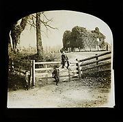 Magic lantern slide of children by gate entrance with mysterious looking ivy covered house standing on smack hill in field behind, England, UK c 1900- 1910