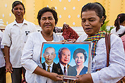 """30 JANUARY 2013 - PHNOM PENH, CAMBODIA:    Women mourning Cambodian King Norodom Sihanouk hold up a portrait of the King (center) with his wife and son. Sihanouk (31 October 1922- 15 October 2012) was the King of Cambodia from 1941 to 1955 and again from 1993 to 2004. He was the effective ruler of Cambodia from 1953 to 1970. After his second abdication in 2004, he was given the honorific of """"The King-Father of Cambodia."""" Sihanouk held so many positions since 1941 that the Guinness Book of World Records identifies him as the politician who has served the world's greatest variety of political offices. These included two terms as king, two as sovereign prince, one as president, two as prime minister, as well as numerous positions as leader of various governments-in-exile. He served as puppet head of state for the Khmer Rouge government in 1975-1976. Most of these positions were only honorific, including the last position as constitutional king of Cambodia. Sihanouk's actual period of effective rule over Cambodia was from 9 November 1953, when Cambodia gained its independence from France, until 18 March 1970, when General Lon Nol and the National Assembly deposed him. Upon his final abdication, the Cambodian throne council appointed Norodom Sihamoni, one of Sihanouk's sons, as the new king. Sihanouk died in Beijing, China, where he was receiving medical care, on Oct. 15, 2012. His cremation is scheduled to take place on Feb. 4, 2013. Over a million people are expected to attend the service.        PHOTO BY JACK KURTZ"""