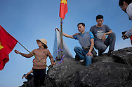 Hikers celebrate their climb to the the top of Mt. Fansipan, the highest mountain in Indochina, Lao Cai Province, Vietnam, Southeast Asia