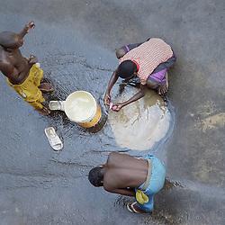 Crianças a brincarem com água num buraco no meio da rua um Luanda, um poço formado devido a uma ruptura na conduta de água da EPAL. Luanda, Angola