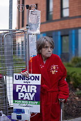 "© Licensed to London News Pictures . 13/10/2014 . Salford , UK . A patient in a dressing gown carrying a crutch and a drip , joins the protest outside the hospital . NHS staff picket outside the Salford Royal (formerly "" Hope "") Hospital in Greater Manchester as nurses, midwives and ambulance staff stage a four hour strike over pay .  Photo credit : Joel Goodman/LNP"