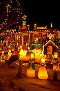 Outdoor lighted Christmas scene in snowy yard of house. St Paul Minnesota USA