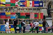 London visitors for the 2012 Olympics admire the 'House of Flags' a structure of 206 panels containing the flag icons of all the countries participating in the London 2012 Olympics and Paralympics. Designed by AY Atchitects, the structure is opposite the Palace of Westminster in Parliament Square. On the far right is the statue of Oliver Cromwell.