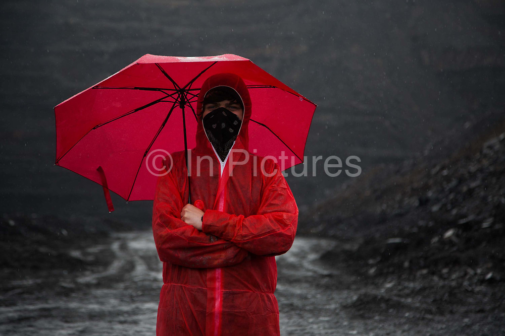 Hundreds of environmental activists stopping the open cast coal mine Ffos-y-Fran near Merthyr Tydfil, Wales from operating May 3rd 2016. An activist in red stands in the black mine under a red umbrella in the rain. The activists from Reclaim the Power wants the mine shut down and a moratorium on all future open coal mining in Wales. Open coal mining is hugely damaging to the environment and  contributing to global climate change.