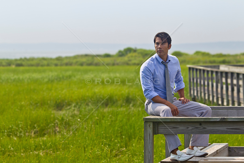 Asian American man in shirt and tie on a walkway in Southampton, NY