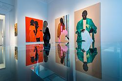 """© Licensed to London News Pictures. 28/10/2020. LONDON, UK.  A staff member poses at the preview of """"Becoming as well as Being"""", an exhibition of new works by Ghanaian painter Kwesi Botchway, many created during the COVID-19 pandemic lockdown. Curated by Ekow Eshun at the inaugural London space of Gallery 1957, the exhibition runs 28 October to 13 December.  Photo credit: Stephen Chung/LNP"""