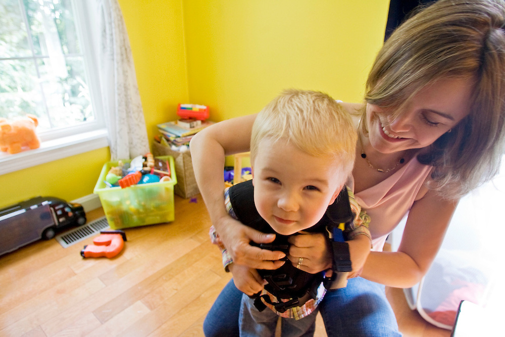 SOUTHBURY, CT - 15 SEPTEMBER 2009 -091509JT03-.Lauren Brenneman clips her son Isaac, 2, into his vest at their Southbury home on Tuesday. The two have cystic fibrosis, an inherited disease that affects the lungs and digestive system, and the vests are used to clear the air passage of the lungs . The two wear the vest at least twice a day for at least 30 minutes at a time. Lauren is helping organize the 10th annual Evening of Comedy of Hope to benefit the Cystic Fibrosis Foundation on Saturday, Sept. 26 at the Heritage Hotel in Southbury. For more information, contact Cassandra Davis at the Cystic Fibrosis Foundation at 860-257-6907..Josalee Thrift Republican-American