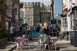 Windsor, UK. 16th April, 2021. Tables are arranged in the street outside a restaurant close to the King Henry VIII gateway to Windsor Castle on the eve of the funeral of Prince Philip. Restaurants and cafes will not be permitted to have tables outside on the day of the funeral.