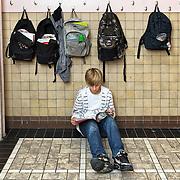 Nederland Rotterdam 23-09-2009 20090923 Serie over onderwijs,   openbare scholengemeenschap mavo, havo en vwo.  Jongen neemt lesstof door op de gang tijdens tussenuur.    Boven hem hangen boekentassen op de knaapjes.                                          .Foto: David Rozing