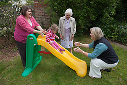 Family group four generations of females with slide in garden