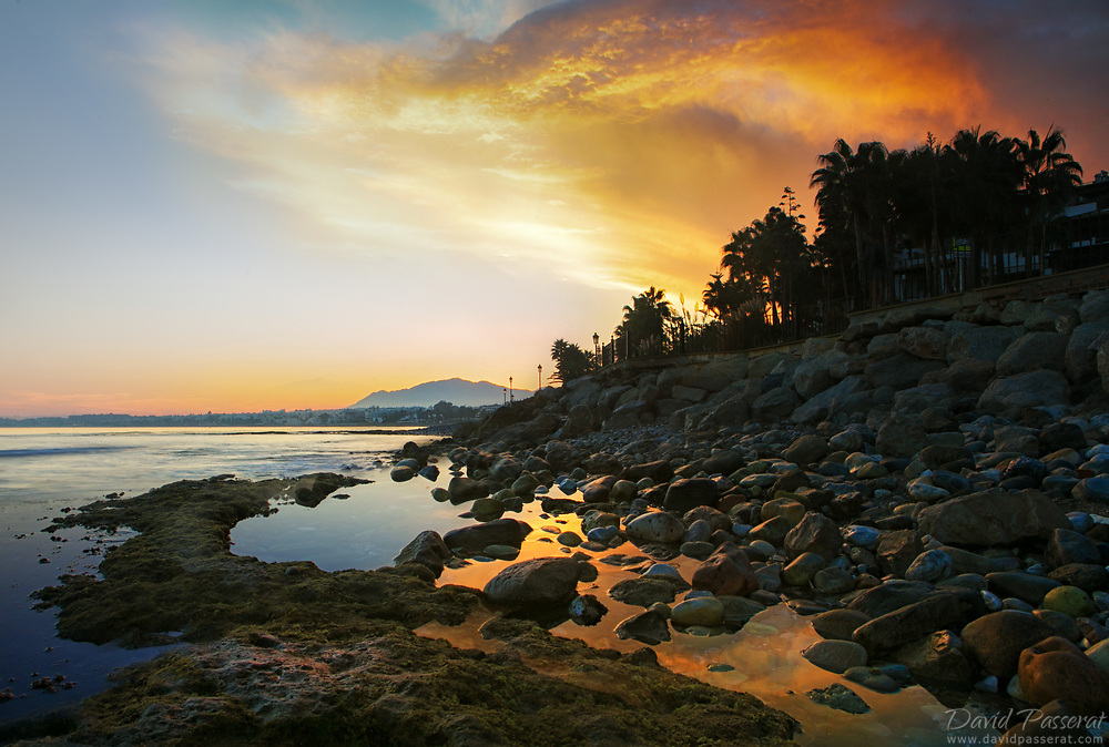 Marbella rocky seascape at low tide during sunset.