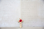 A memorial cross with a poppy on it placed up against the wall, containing the names of hundreds of fallen soldiers that died during the First and Second World War. Faubourg DAmiens cemetery is the burial site of 2678 identified casualties and a memorial to thousands more from the First and Second World War.  It is looked after and managed by the Commonwealth War Graves Commission in the town of Arras, France.