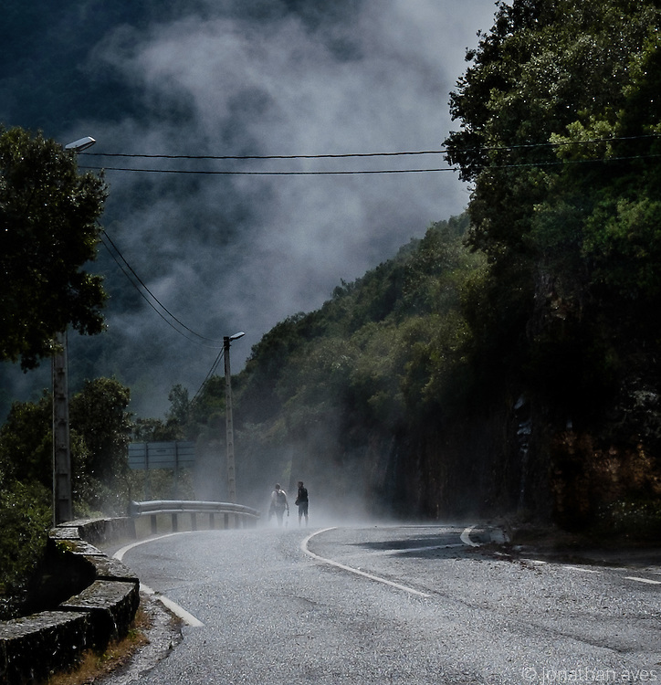 A storm hits two travellers as they walk to the Monastery of Santo Toribio de Liébana, Cantabria, Northern Spain