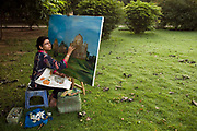 A woman paints a picture of a monument in Lodhi Gardens, New Delhi, India
