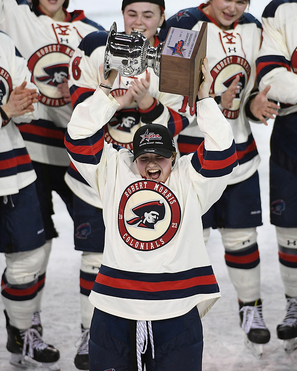 ERIE, PA - MARCH 06: Ellie Marcovsky #23 of the Robert Morris Colonials hoists the CHA Championship Trophy after the Colonials defeated the Syracuse Orange 1-0 in the championship game at the Erie Insurance Arena on March 6, 2021 in Erie, Pennsylvania. (Photo by Justin Berl/Robert Morris Athletics)