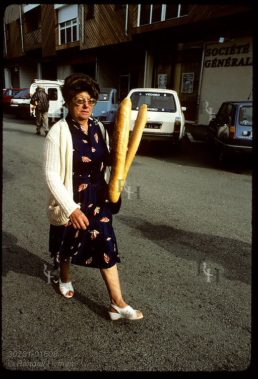Woman walking home from bakery with her day's supply of French bread; Carnac, Brittany. France