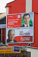 "two bill board posters for lech kaczynski party showing his face and red and white background in krakow poland. the writing reads ""lech kaczynski - silny prezydent uczciwa polska"""