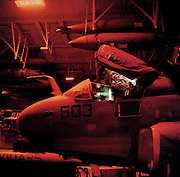 An EA-6B Prowler intelligence-gathering patrol aircraft is worked on in the hangar deck of the US Navy's Harry S Truman aircraft carrier whilst on exercise somewhere in the Persian Gulf. Red light shines down from overhead lighting as the crewman carries on his work, servicing the plane. The Truman is the largest and newest of the US Navy's fleet of new generation carriers, a 97,000 ton floating city with a crew of  5,137, 650 are women. The Iraqi no-fly zones (NFZs) were proclaimed by the United States, United Kingdom and France after the Gulf War of 1991 to protect humanitarian operations in northern Iraq and Shiite Muslims in the south. Iraqi aircraft were forbidden from flying inside the zones. The policy was enforced by US, UK and French aircraft patrols until France withdrew in 1998.