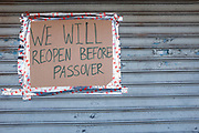 Brooklyn, NY - 26 March 2020. Residents of New York City have been asked to stay home as a result of the novel coronavirus, and all but essential businesses have been asked to close. In Brooklyn's Midwood neighborhood, many businesses have their shutters rolled down, and the few that are open limit the number of people who can enter. A kosher pizza shop has oits shutters rolled down, but hopes to open before Passover.