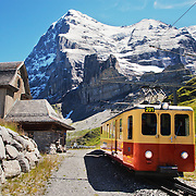 The Jungfraubahn train which transports tourists to Jungfraujoch railway station, highest railway station in Europe (3,454 meters), from Kleine Scheidegg and the town of Grindelwald below. It's located near Mount Eiger, Monch and Jungfrau in the Bernese Alps.<br /> <br /> + ART PRINTS +<br /> To order prints or cards of this image, visit:<br /> http://greg-stechishin.artistwebsites.com/featured/jungfraubahn-train-1-greg-stechishin.html