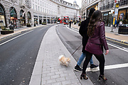 With very few people out and about the scene on Regent Street is one of emptiness as dog walkers pass and the national coronavirus lockdown three continues on 29th January 2021 in London, United Kingdom. Following the surge in cases over the Winter including a new UK variant of Covid-19, this nationwide lockdown advises all citizens to follow the message to stay at home, protect the NHS and save lives.