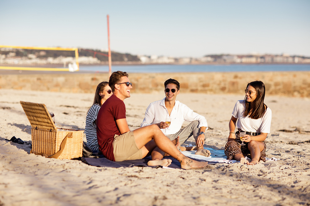 People socialising and enjoying a picnic on the sand at the Gunsite in Jersey, Channel Islands