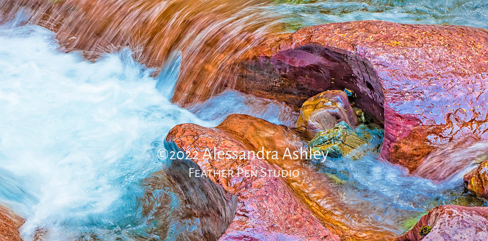 Rushing water highlights colored rocks at Avalanche Gorge, Glacier National Park, Montana.