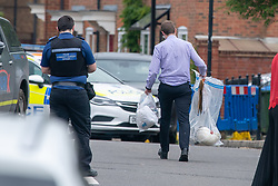 """© Licensed to London News Pictures. 02/06/2021. Aylesbury, UK. A police investigator carries evidence bags, one containing a hard hat, following a fatal incident, believed to involve an electrical worker, in Fairford Leys Way, Aylesbury. South Central Ambulance Service (SCAS) were called at 11:30am and sent a rapid response vehicle, ambulance crew, ambulance o fficer and the Thames Valley Air Ambulance to assist one patient. A Thames Valley Police spokesperson said: """"This was the sudden death of a man in Fairford Leys Road, Aylesbury, which was reported at around 11.40am today (2/6). Officers attended along with paramedics. Next of kin have been made aware and are being supported. The death is not being treated as suspicious."""" Photo credit: Peter Manning/LNP"""