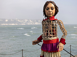 © Licensed to London News Pictures. 19/10/2021. Folkestone, UK. Little Amal, a giant puppet, performs on the Harbour Arm at Folkestone in Kent. The 3.5m tall puppet, worked by a team of puppeteers, has been on a journey starting from Turkey in July, visiting Greece, Italy, Switzerland, Germany, Belgium and France.  Little Amal, whose name means hope in Arabic, represents the journey of a nine year old girl from Syria. Photo credit: Peter Macdiarmid/LNP