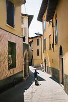 TOSCOLANO MADERNO, ITALY - 19 APRIL 2018: A child rides his bike the historical centre of Toscolano Maderno, Italy, on April 19th 2018.<br /> <br /> Lake Garda is the largest lake in Italy. It is a popular holiday location located in northern Italy, about halfway between Brescia and Verona, and between Venice and Milan on the edge of the Dolomites. The lake and its shoreline are divided between the provinces of Verona (to the south-east), Brescia (south-west), and Trentino (north).