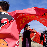 Gerald Ben, right, Matthew Yazzie and other members of the boys basketball team hang banners on their float during a parade at Saint Michael High School in Saint Michaels Friday.