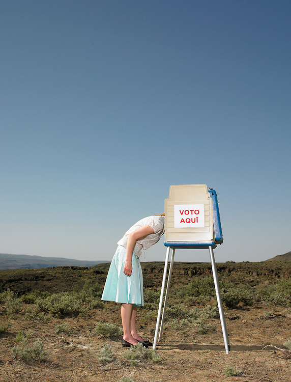 Woman sticking head in voting booth outdoors.