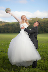 Groom lifting up bride in field, Ammersee, Upper Bavaria, Bavaria, Germany