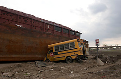 04 November, 2005.  New Orleans, Louisiana. Post Katrina. <br /> After Katrina, New Orleans, Louisiana. Two months after Hurricane Katrina smashed the Lower 9th Ward, the floods have receded but the devastation remains. A school bus remains trapped by a barge that washed through the levee, flooding the area.<br /> Photo; ©Charlie Varley/varleypix.com