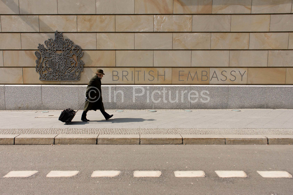 A pedestrian pulling a suitcase walks past the exterior of the British Embassy, the United Kingdom's diplomatic mission to Germany in Berlin. It is located on 70-71 Wilhelmstraße, near the Hotel Adlon. Upon reunification in 1991, an architectural competition was won by Michael Wilford and the new building opened by Queen Elizabeth II on 18 July 2000.
