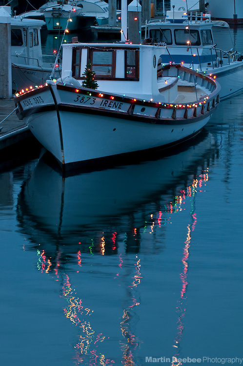 Christmas lights on fishing boat docked in Pillar Point Harbor in Half Moon Bay, California. The Irene is a 38-foot Monterey class fishing boat built in 1925, which was restored in 2008 by the Pillar Point Educational Fund.