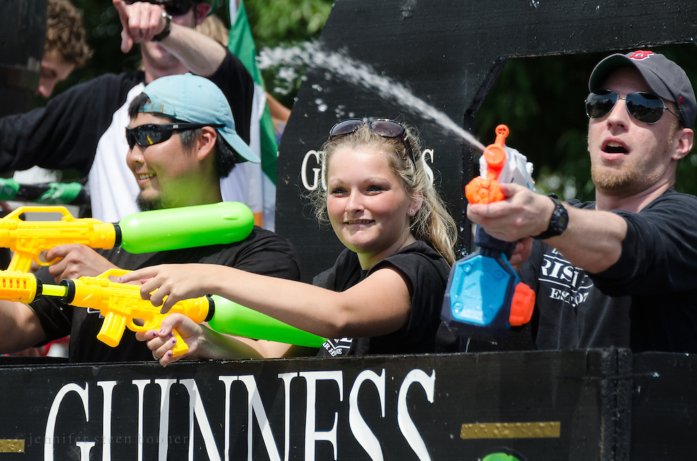 BAR HARBOR, MAINE, July 4, 2014. Riders on a float in the Independence Day Parade shoot water guns at the crowd.
